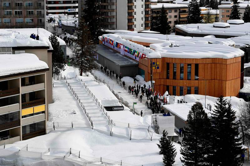 Gendarmes of the cantonal police (top L) stand on a roof to monitor the area near the Davos Congress Centre (R), the venue of the annual World Economic Forum (WEF), in the town of Davos, eastern Switzerland, on January 25, 2018. / AFP PHOTO / Miguel MEDINA
