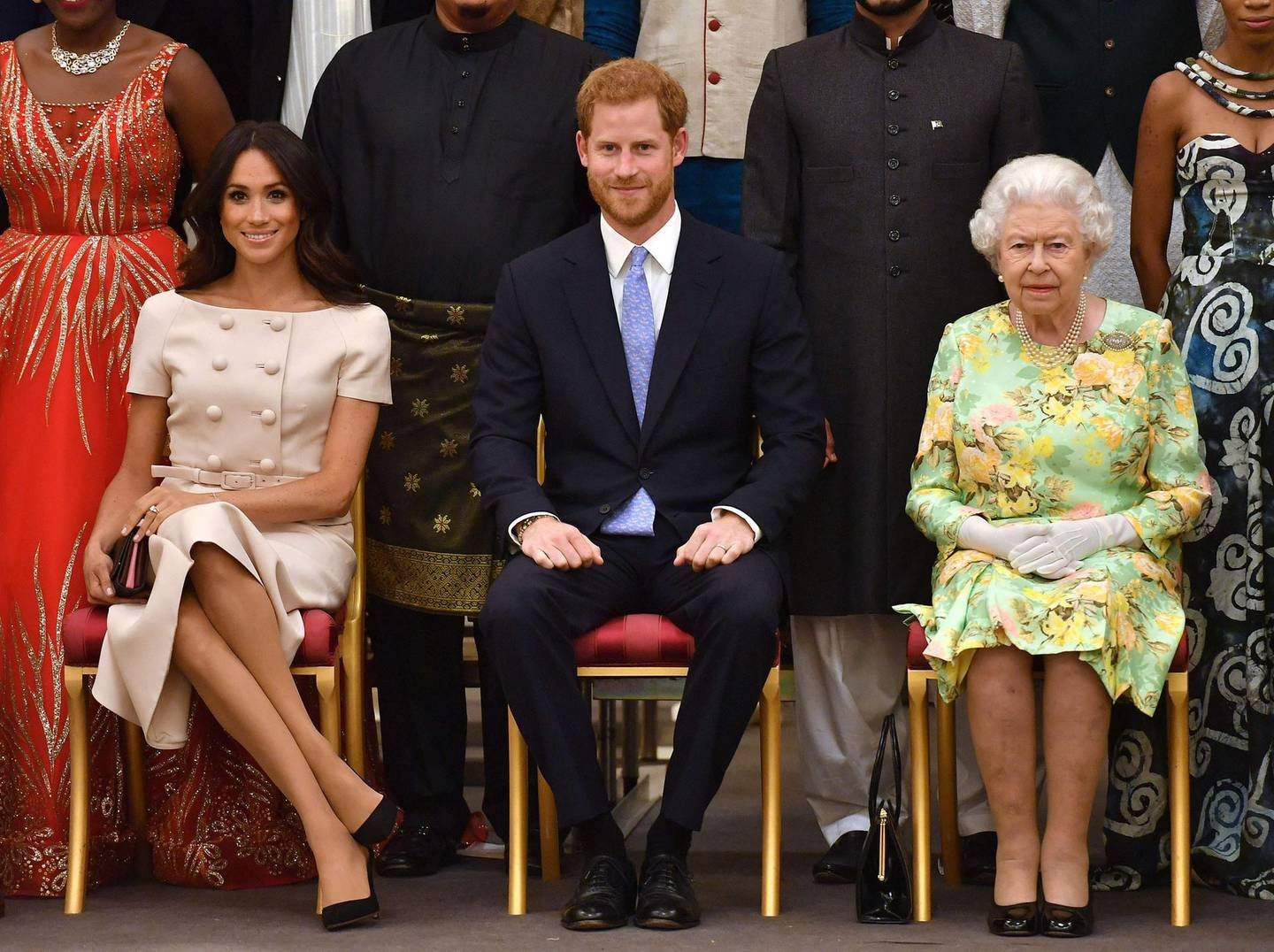 """(FILES) In this file photo taken on June 26, 2018 (L-R) Meghan, Duchess of Sussex, Britain's Prince Harry, Duke of Sussex and Britain's Queen Elizabeth II pose for a picture during the Queen's Young Leaders Awards Ceremony at Buckingham Palace in London.     Queen Elizabeth II is saddened by the challenges faced by her grandson Prince Harry and his wife Meghan, and takes their allegations of racism in the royal family seriously, Buckingham Palace said on March 9, 2021. """"The whole family is saddened to learn the full extent of how challenging the last few years have been for Harry and Meghan. The issues raised, particularly that of race, are concerning,"""" the palace said in a statement released on the queen's behalf. / AFP / POOL / John Stillwell"""