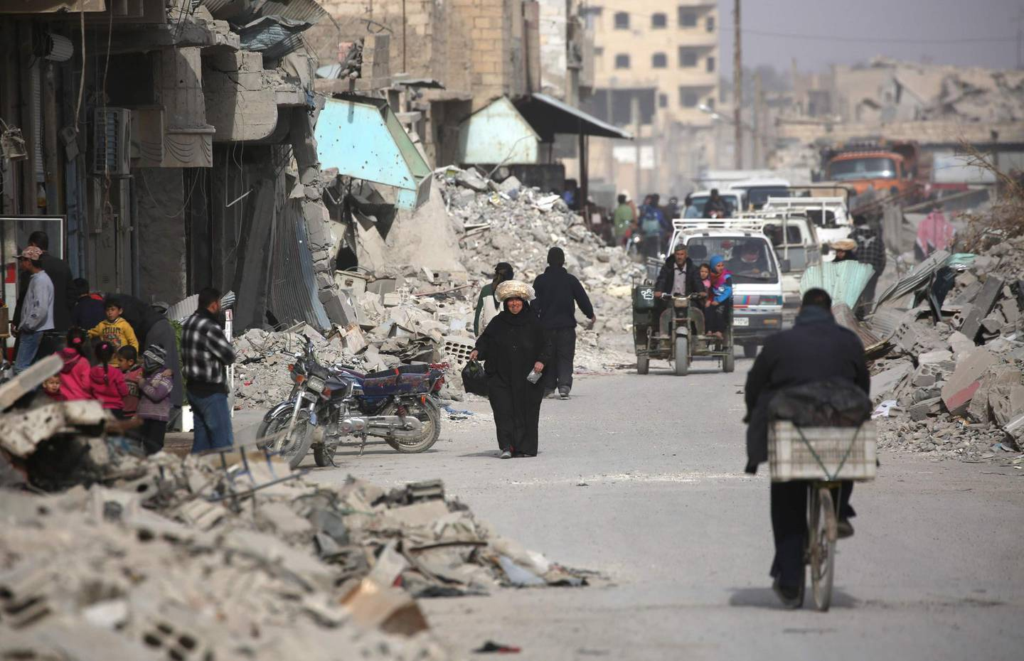 Syrians walk amidst the debris of destroyed buildings in the northern Syrian city of Raqa, on January 11, 2018 after a huge military operation led on the ground by Kurdish fighters and in the air by US warplanes defeated jihadists from the Islamic State group but also left the city completely disfigured. Once home to around 300,000 people, Raqa's neighbourhoods were empty when it was declared retaken in mid-October. Three months on, despite the lack of infrastructure and the lingering threat of unexploded mines and bombs, a trickle of residents -- a few hundred families -- are attempting to return.  / AFP PHOTO / DELIL SOULEIMAN