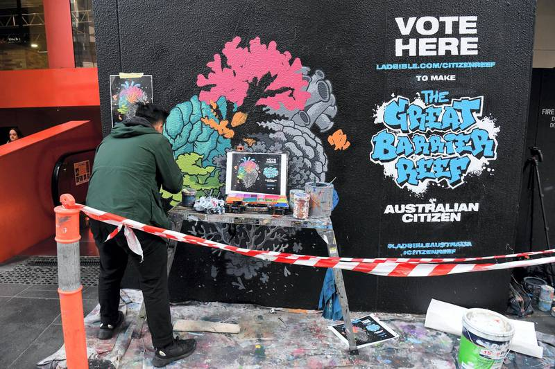 Artist Ed Wong paints a mural depicting coral in the shape of an anatomical heart with half of the heart deteriorating, representing the half of the Great Barrier Reef that has been bleached to death due to climate change, along a street in Melbourne on July 31, 2019. - Over 25,000 Australians have signed a petition to grant the Great Barrier Reef Australian citizenship in order to gain the reef the same rights and protections as all Australian citizens. (Photo by William WEST / AFP) / RESTRICTED TO EDITORIAL USE - MANDATORY MENTION OF THE ARTIST UPON PUBLICATION - TO ILLUSTRATE THE EVENT AS SPECIFIED IN THE CAPTION