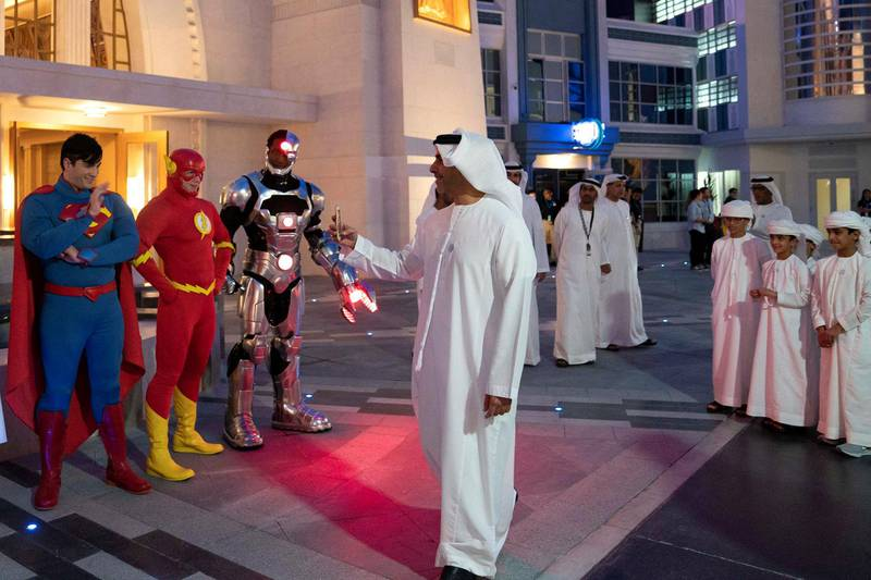 YAS ISLAND, ABU DHABI, UNITED ARAB EMIRATES - July 23, 2018: HHH Lt General Sheikh Saif bin Zayed Al Nahyan, UAE Deputy Prime Minister and Minister of Interior (C), takes a photo of super heroes during the opening of Warner Bros World Abu Dhabi.   ( Eissa Al Hammadi for The Crown Prince Court ) ---