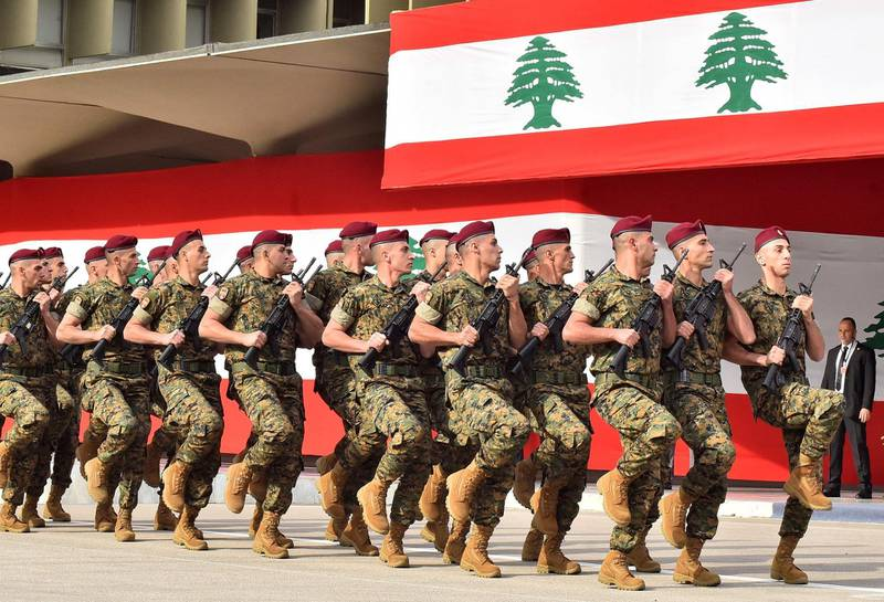 (FILES) In this file photo taken on November 22, 2019 Lebanese army soldiers march before the president, prime minister, and parliament speaker during a military parade commemorating the 76th anniversary of Lebanese independence from France at the Defence Ministry headquarters in Yarze near the presidential palace of Baabda southeast of the capital. Lebanon is unable to pay its soldiers enough, the army warned on June 16, 2021 ahead of a UN-backed conference during which donors will seek to shore up one of the bankrupt country's key institutions.  / AFP / -