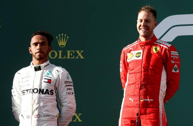 Formula One F1 - Australian Grand Prix - Melbourne Grand Prix Circuit, Melbourne, Australia - March 25, 2018  Ferrari's Sebastian Vettel celebrates his win on the podium with Mercedes' Lewis Hamilton  REUTERS/Brandon Malone