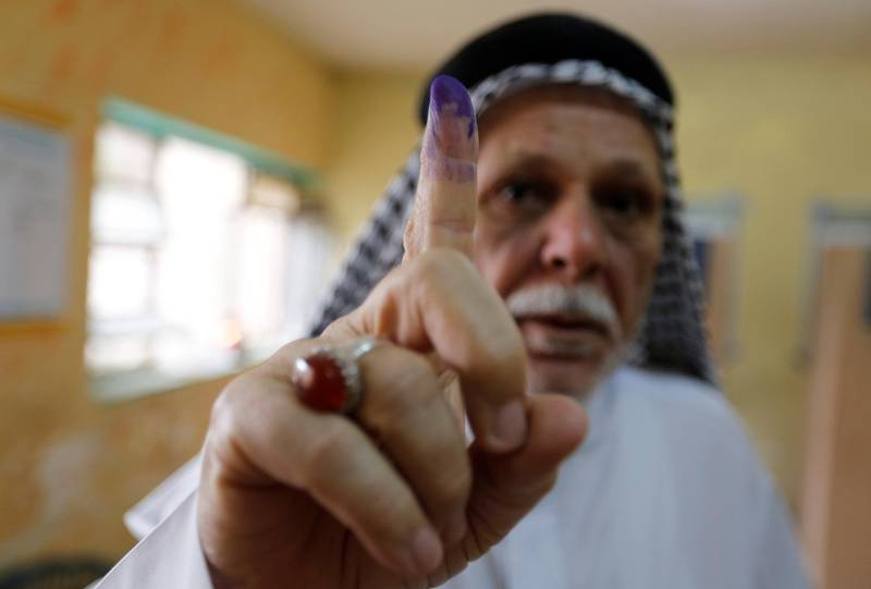 An Iraqi man shows his ink-stained finger after casting his vote at a polling station during the parliamentary election in the Sadr city district of Baghdad, Iraq May 12, 2018. REUTERS/Wissm al-Okili
