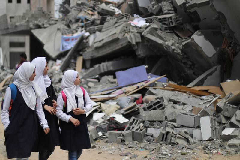Palestinian students look at a building that was destroyed by Israeli air strikes near their damaged school in Gaza City May 7, 2019. REUTERS/Mohammed Salem
