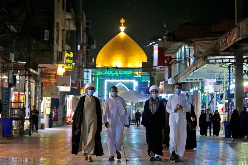 Shiite pilgrims walk outside the shrine of Imam Ali in Najaf, Iraq, Feb. 24, 2020 (AP Photo/Anmar Khalil)