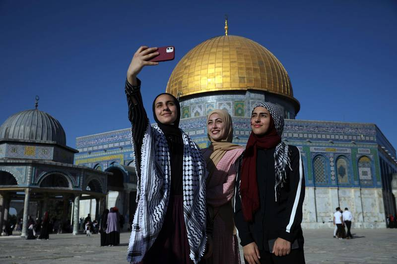 CORRECTS DATE TO MAY 13 - Women pose for a selfie for Eid al-Fitr at the Dome of the Rock Mosque in the Al-Aqsa Mosque compound in the Old City of Jerusalem, Thursday, May 13, 2021. Eid al-Fitr, festival of breaking of the fast, marks the end of the holy month of Ramadan. (AP Photo/Mahmoud Illean)