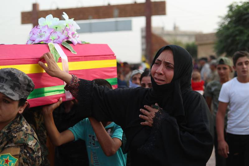 """Syrian mourn by the bodies of four fighters of the Syrian Democratic Forces (SDF), during their funeral in the northeastern city of Qamishli on September 14, 2018. Four SDF fighters were killed during battles in Deir Ezzor to oust Islamic State jihadists from the town of Hajin on the east bank of the Euphrates, the most significant remnant of the sprawling """"caliphate"""" the jihadists once controlled spanning Syria and Iraq. / AFP / Delil SOULEIMAN"""
