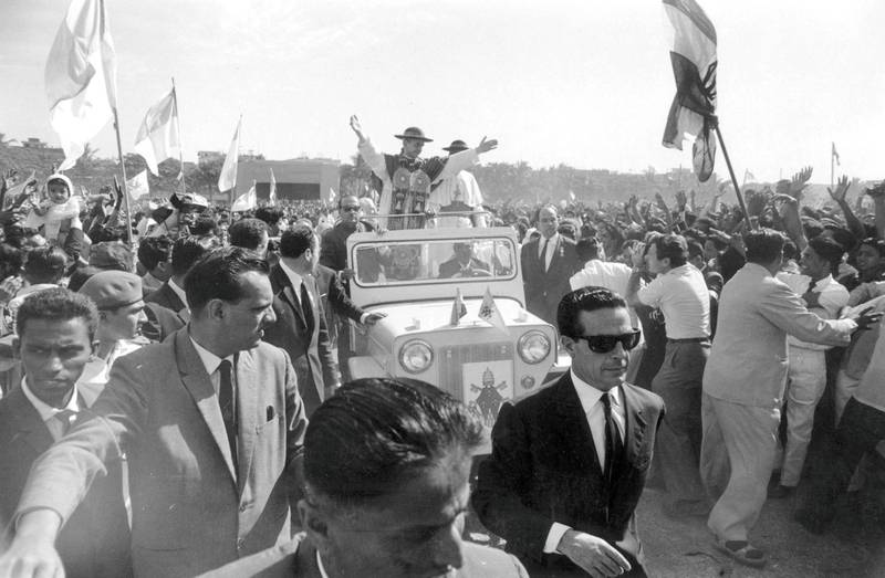 5th December 1964:  During a visit to the John Bosco School in India, Pope Paul VI drives through the crowds with a convoy of bodyguards.  (Photo by Terry Fincher/Express/Getty Images)