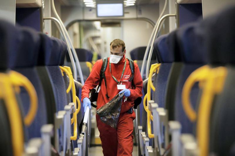 A cleaner sanitizes a wagon on a regional train, at the Garibaldi train station in Milan, Italy, Friday, Feb. 28, 2020. Authorities are taking new measures to sanitize trains and public transportation after the COVID-19 virus outbreak. (AP Photo/Luca Bruno)
