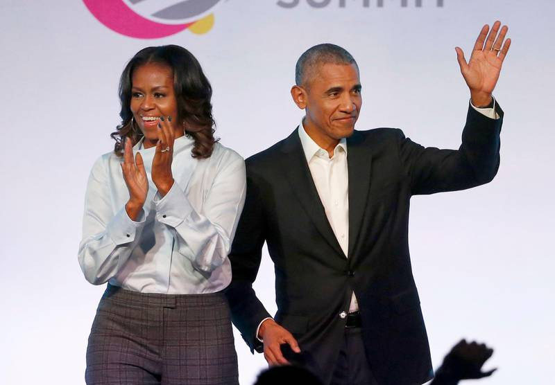 """FILE - In this Oct. 31, 2017, file photo, former President Barack Obama, right, and former first lady Michelle Obama appear at the Obama Foundation Summit in Chicago.  The Obamas have unveiled a slate of projects in development for Netflix, a year after the former president and first lady signed a deal with the streaming platform. The Obamas' production company, Higher Ground Productions, announced Tuesday, April 30, 2019, a total of seven films and series that Barack Obama said will entertain but also """"educate, connect and inspire us all.""""(AP Photo/Charles Rex Arbogast, File)"""