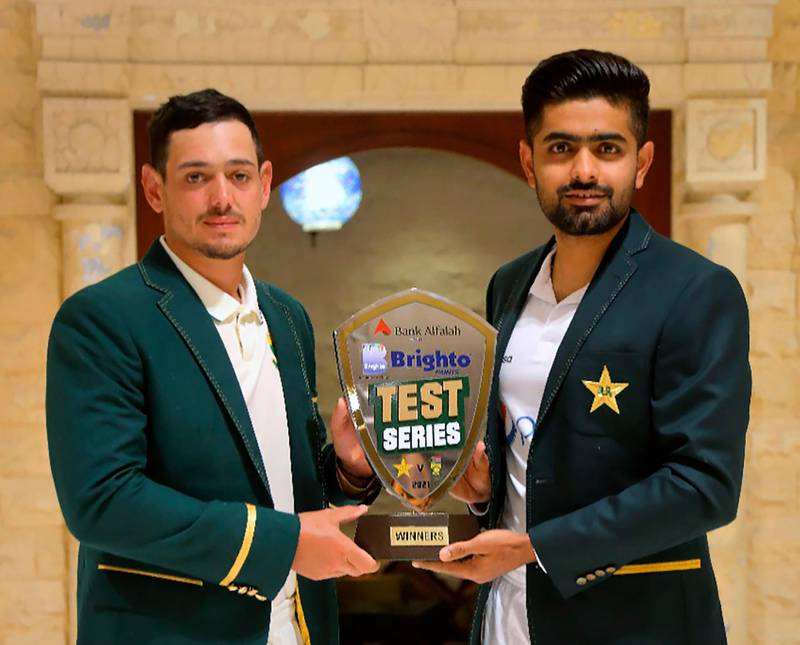 In this photo provided by Pakistan Cricket Board, Pakistan cricket team's skipper, Babar Azam, right, and his South Africa's counterpart Quinton de Kock pose for a photograph with the trophy of test-series, in Karachi, Pakistan, Monday, Jan. 25, 2021. Pakistan and South Africa will play the first test match on Jan. 26. (Pakistan Cricket Board via AP)