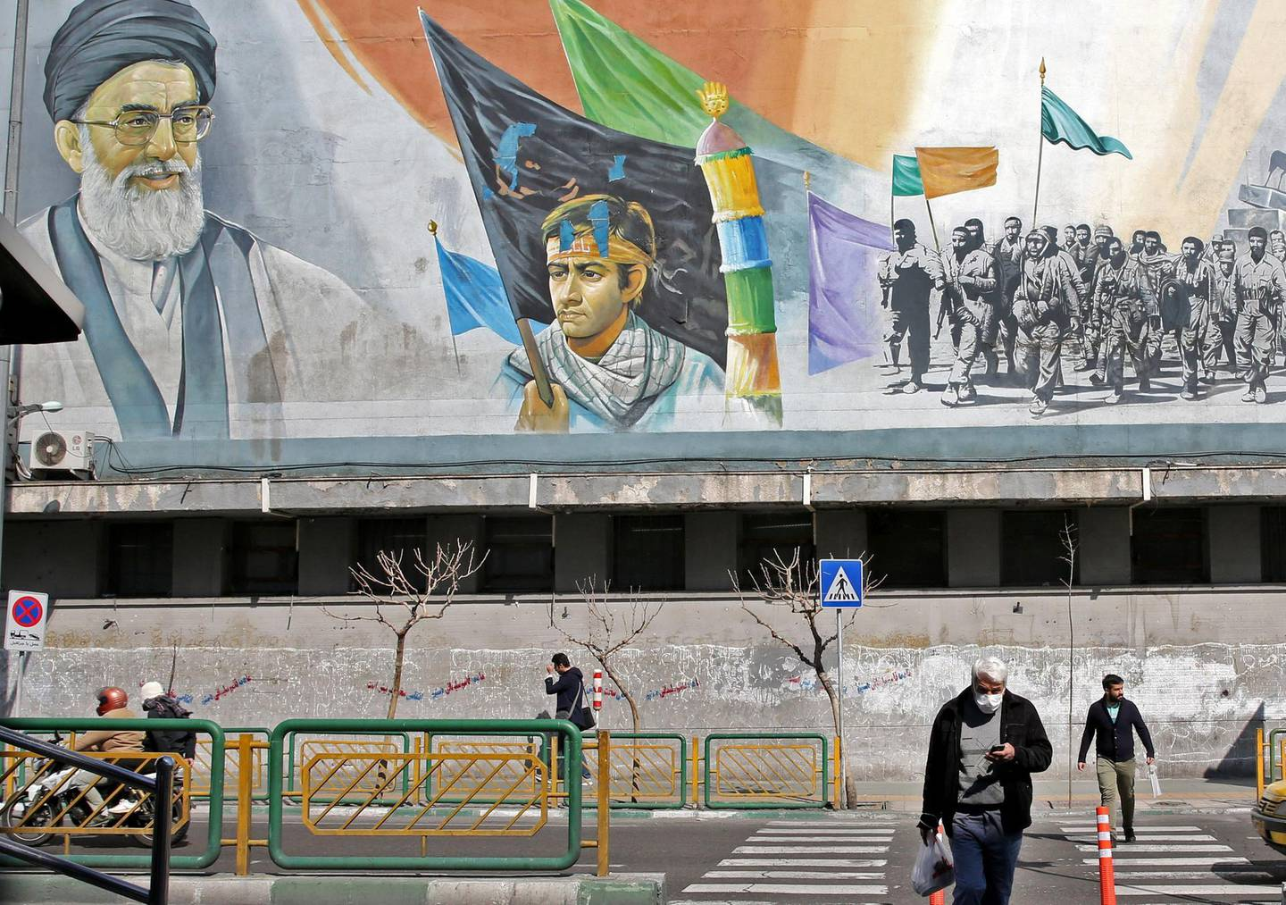 An Iranian man wearing a mask walks under a mural bearing an image of Iran's Supreme Leader Ayatollah Ali Khamenei in Tehran on March 4, 2020. Iran has scrambled to halt the rapid spread of the COVID-19 virus, shutting schools and universities, suspending major cultural and sporting events, and cutting back on work hours.  / AFP / ATTA KENARE