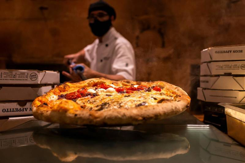 RIO DE JANEIRO, BRAZIL - SEPTEMBER 23: A staff member wearing a face mask prepares a pizza at Mamma Jamma pizzeria in the Botafogo neighborhood on September 23, 2020 in Rio de Janeiro, Brazil. Establishments are adopting preventive measures against the spread of the coronavirus (COVID-19) according to a protocol for the reopening of bars and restaurants in the city of Rio de Janeiro. (Photo by Bruna Prado/Getty Images)