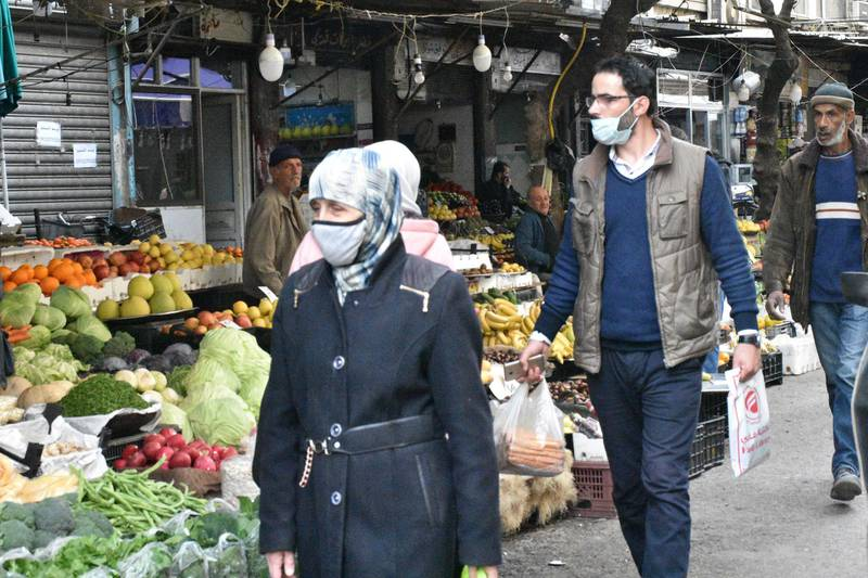 epa08920700 Syrians wearing masks as precautionary measures against the Coronavirus, buy their daily basic food items and other necessities in one of the streets of Damascus, Syria, 05 January 2021.  EPA/YOUSSEF BADAWI