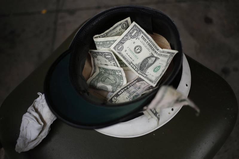 U.S. dollar banknote tips sit in a street musician's hat in the French Quarter of New Orleans, Louisiana, U.S., on Wednesday, Feb. 7, 2018. New Orleans prepares for its most popular tourism time of year as the Mardi Gras festival gets set to parade through the city on the last day of the Carnival season. Photographer: Luke Sharrett/Bloomberg