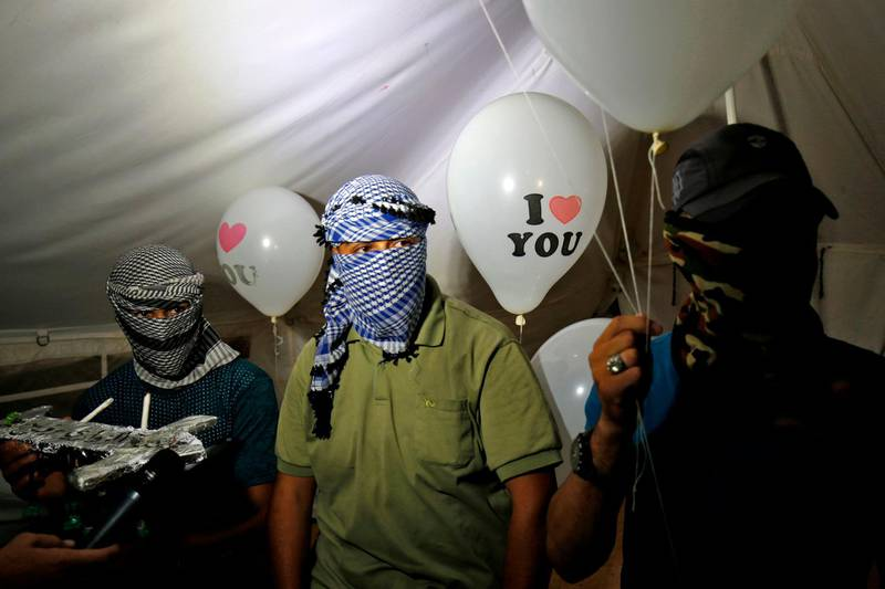 """Masked Palestinian protesters calling themselves the """"night confusion units"""" hold incendiary devices attached to ballons to be flown towards Israel, near the  Gaza-Israel border east of Rafah in the southern Gaza Strip, on September 26, 2018. The border protests since March 30 have been labelled the """"Great March of Return"""" because they call for Palestinian refugees to return to their former homes inside what is now Israel. Hundreds of thousands of dollars in damage were caused to Israeli land -- including incinerated crops -- by the kites and balloons, Israeli authorities said. / AFP / SAID KHATIB"""