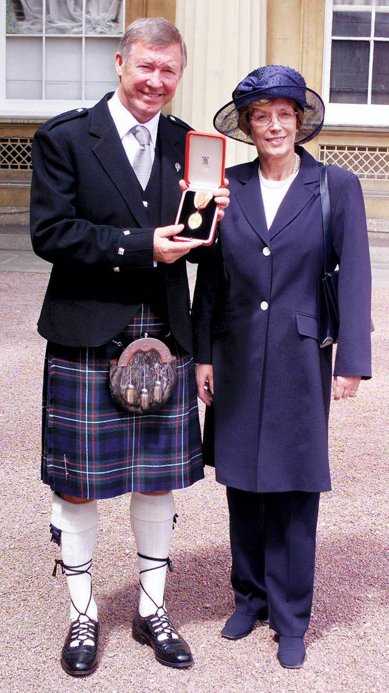 Manchester United manager Sir Alex Ferguson and wife Cathy pose for photographs July 20, 1999. Ferguson was knighted by Britain's Queen Elizabeth II during an investiture ceremony at Buckingham Palace.  REUTERS/Pool  PS/GB - RP1DRILVDWAB