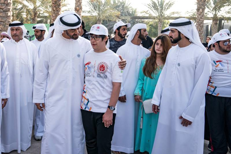 """ABU DHABI, UNITED ARAB EMIRATES - January 26, 2018: HH Sheikh Mohamed bin Zayed Al Nahyan, Crown Prince of Abu Dhabi and Deputy Supreme Commander of the UAE Armed Forces (3rd L), speaks with a participant during the Special Olympics Wold Games Abu Dhabi 2019 initiative """"Walk Unified"""", at Umm Al Emarat Park. Seen with HH Sheikh Hamdan bin Mohamed Al Maktoum, Crown Prince of Dubai (R), and HH Sheikha Al Jalila bint Mohamed bin Rashid Al Maktoum (2nd R).  ( Hamad Al Kaabi / Crown Prince Court - Abu Dhabi ) —"""