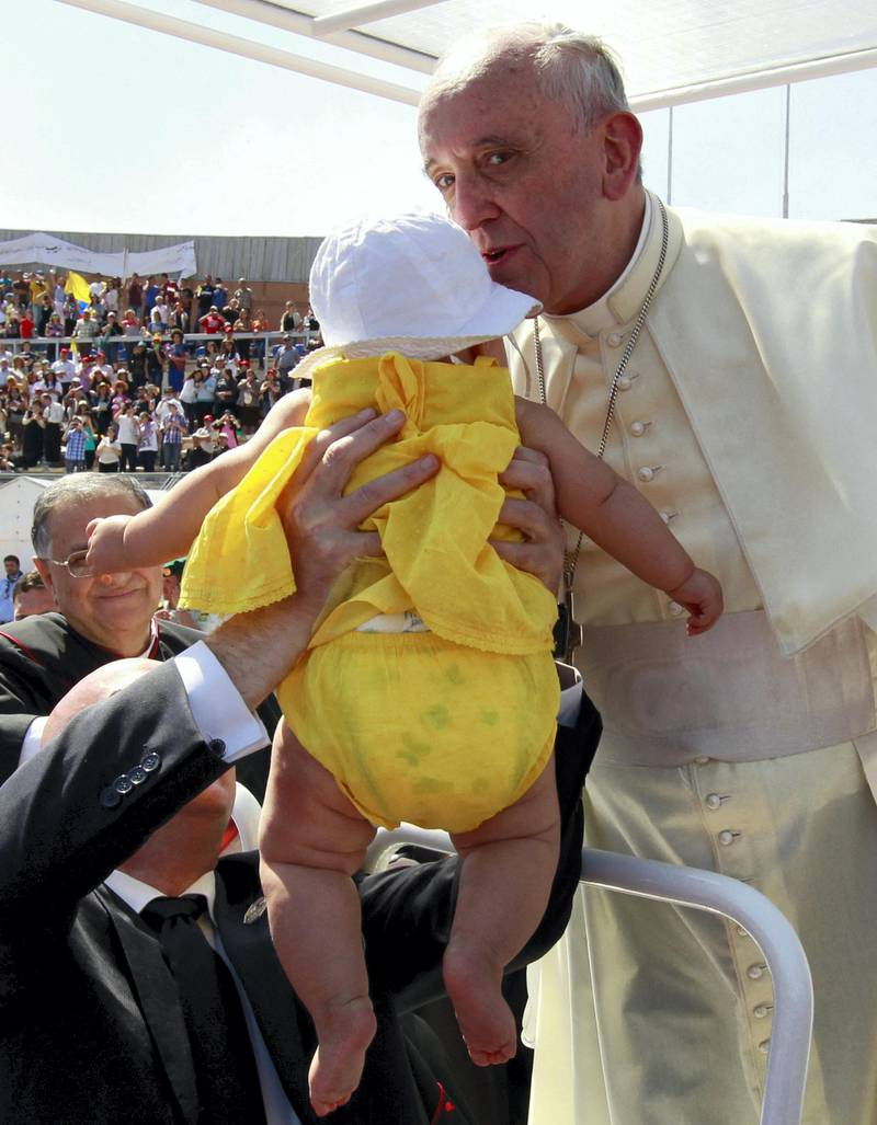 Pope Francis kisses a baby before celebrating a mass at the Amman stadium in the Jordanian capital on May 24, 2014. Pope Francis made an urgent plea today for peace in war-torn Syria as he kicked off a three-day pilgrimage to the Middle East. AFP PHOTO / KHALIL MAZRAAWI (Photo by KHALIL MAZRAAWI / AFP)
