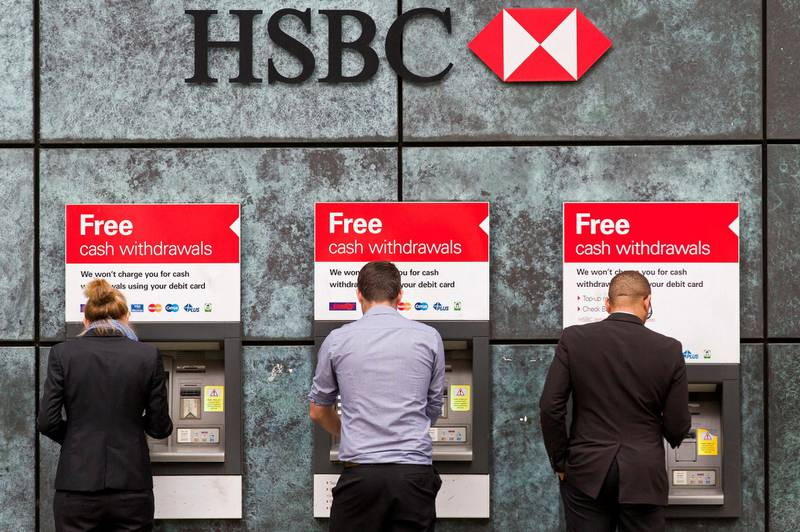 Customers use ATM cashpoints outside a HSBC bank branch in London on June 9, 2015. Scandal-hit bank HSBC said it would cut its global headcount by up to 50,000 as part of a restructuring that entails its withdrawal from Brazil and Turkey, while it also mulls abandoning London as its HQ.   AFP PHOTO / JUSTIN TALLIS (Photo by JUSTIN TALLIS / AFP)