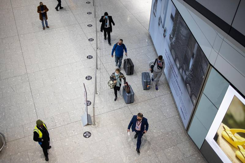"""LONDON, ENGLAND - FEBRUARY 15: Passengers arriving at Heathrow's Terminal 5 are escorted by security personal on February 15, 2021 in London, England. From today, people arriving from 33 """"red list"""" countries, including South Africa and the United Arab Emirates, must isolate in hotels rooms for 10 days at their own expense. The policy was announced late last month in response to the emergence of new variants of the novel coronavirus that are more resistant to existing vaccines. (Photo by Dan Kitwood/Getty Images)"""