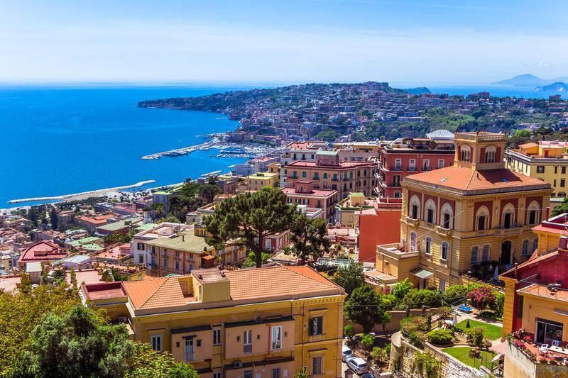 Aerial view from hilltop over Naples, Italy. View on Old Town of Naples from Castel Sant'Elmo. Sunny spring day. Many colorful buildings and gulf of Naples.
