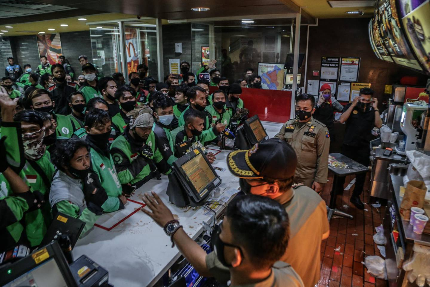 Food delivery riders queue up at a McDonald's outlet in Bogor on June 9, 2021, to buy the new BTS-meal deal for hungry fans in the K-Pop mad country, causing more than a dozen McDonald's outlets to temporarily shuttered over virus fears. / AFP / ADITYA AJI