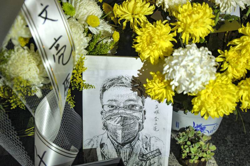 """This photo taken on February 7, 2020 shows a photo of the late ophthalmologist Li Wenliang with flower bouquets at the Houhu Branch of Wuhan Central Hospital in Wuhan in China's central Hubei province. - Li, a doctor who was punished after raising the alarm about the new coronavirus, died on February 7 after being infected by the pathogen. The death toll from the novel coronavirus surged past 800 in mainland China, overtaking global fatalities in the 2002-03 SARS epidemic, even as the World Health Organization said the outbreak appeared to be """"stabilising"""". (Photo by STR / AFP) / China OUT"""