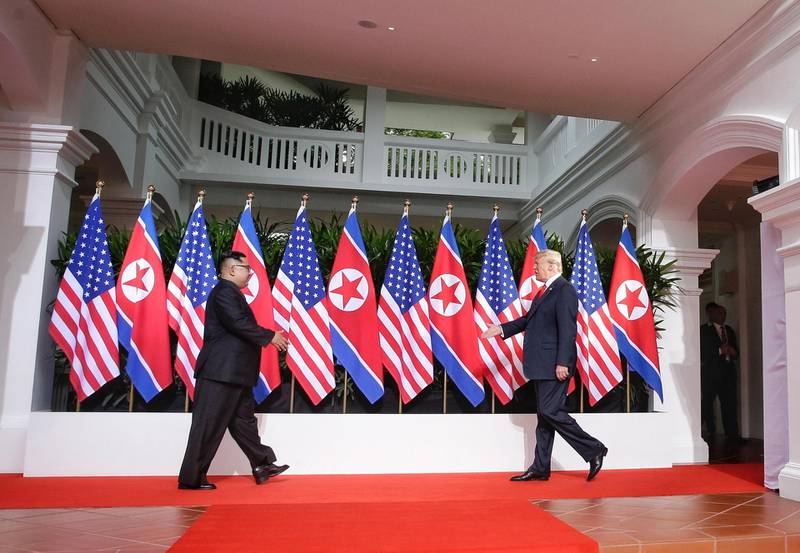 epaselect epa06801414 US President Donald J. Trump (R) and North Korean leader Kim Jong-un (L) walk towards each other to shake hands at the start of a historic summit at the Capella Hotel on Sentosa Island, Singapore, 12 June 2018. The summit marks the first meeting between an incumbent US President and a North Korean leader.  EPA/KEVIN LIM / THE STRAITS TIMES   EDITORIAL USE ONLY