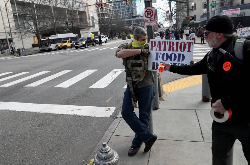 """Stickers reading """"Guns save lives"""" are put on a food drive sign as armed people stand on a corner near the Virginia State Capitol while a caravan of cars drives by in support of second amendment rights, in Richmond, Virginia, U.S. January 18, 2021. REUTERS/Leah Millis"""