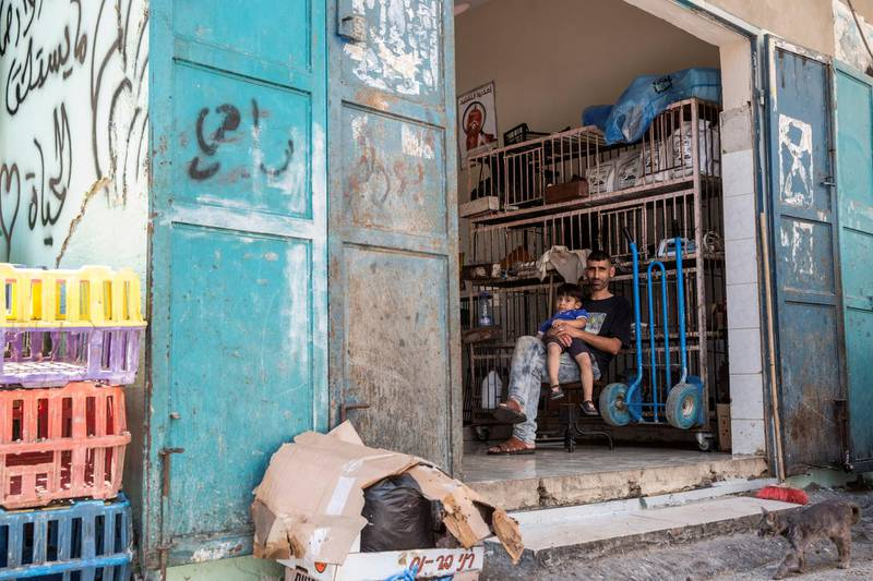 Rami Qweis waits for customers to shop in his meat store with his son in the Aida refugee camp near Bethlehem on June 23,2019.Photo by Heidi Levine for The National