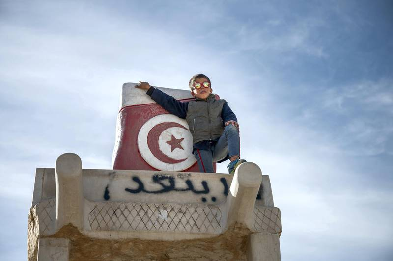 A young boy at the top of a giant wheelbarrow structure created in memory of Mohamed Bouazizi in Sidi Bouzid.