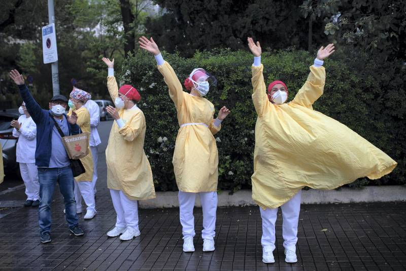 -- AFP PICTURES OF THE YEAR 2020 --  Heathcare workers wearing face masks and protective suits acknowledge applause outside the Hospital de Barcelona on April 13, 2020 in Barcelona, during a national lockdown to prevent the spread of the COVID-19 disease. - Spain reopened parts of its coronavirus-stricken economy on Monday as slowing death tolls in some of the worst-hit countries boosted hopes the outbreak may be peaking and lockdowns could soon be eased. (Photo by Josep LAGO / AFP)