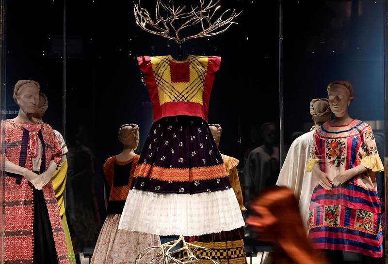 An employee poses as she walks past dresses and tunics forming part of 'Frida Kahlo:Making Herself Up',  an exhibition of the Mexican artist's possessions which goes on display outside of Mexico for the first time, at the Victoria and Albert Museum in London, Britain, June 13, 2018. REUTERS/Toby Melville