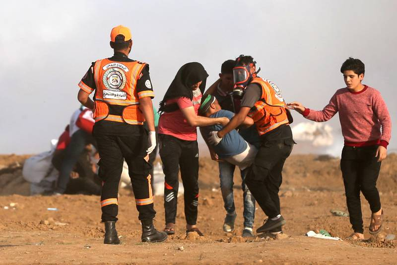 Palestinians carry an injured protester during clashes with Israeli forces along the border with the Gaza strip east of Jabalia on May 18, 2018.  / AFP / MOHAMMED ABED