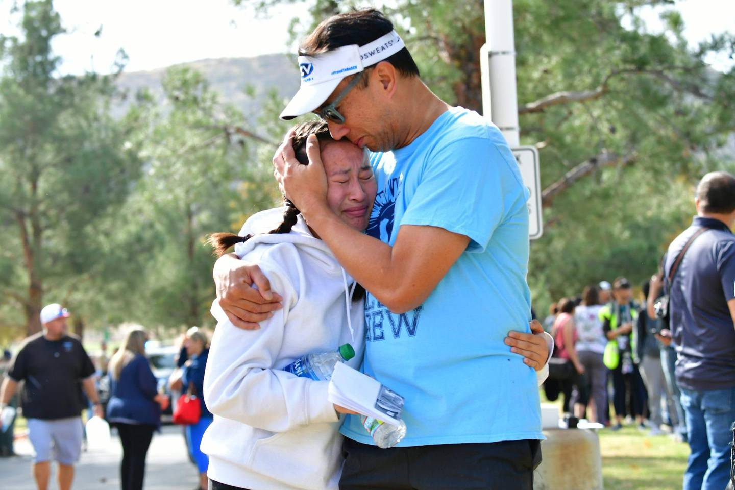"""TOPSHOT - A man embraces his daughter after picking her up at Central Park, after a shooting at Saugus High School in Santa Clarita, California on November 14, 2019. At least four people were injured in a shooting at a high school north of Los Angeles Thursday, triggering a police hunt for the suspect who was later taken into custody.One female was killed Thursday, hospital officials said. The suspect was in custody and taken to a hospital for treatment, while at least three others were injured in the shooting at Saugus High School in Santa Clarita, 40 miles (65 kilometers) north of Los Angeles.""""One female deceased patient. Two critical male patients. One male patient in good condition,"""" tweeted the nearby Henry Mayo Hospital in Valencia.No further details of the deceased were provided.   / AFP / Frederic J. BROWN"""