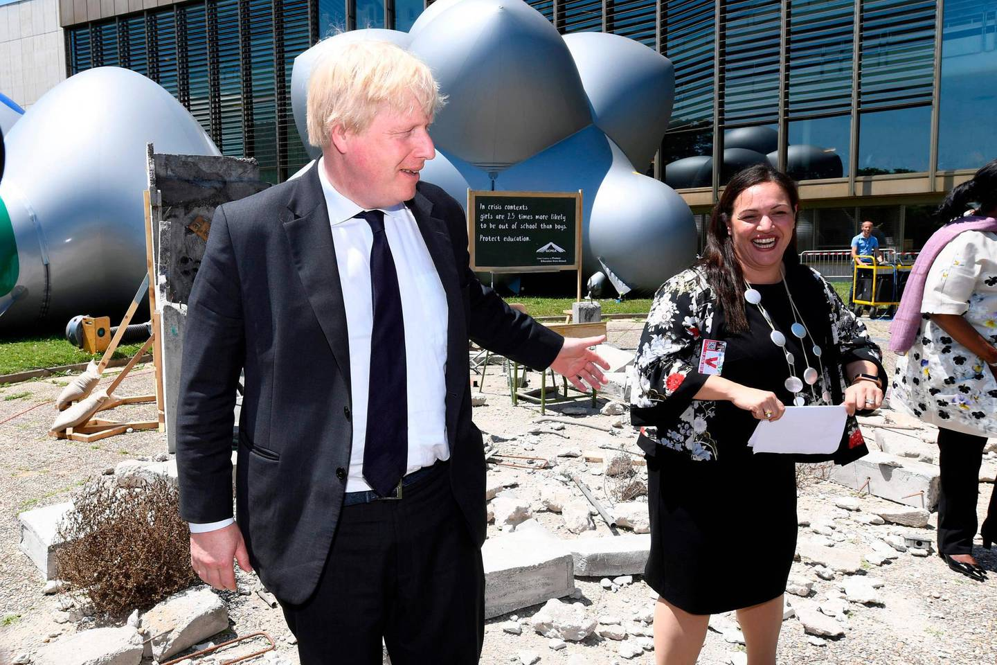 British Foreign Secretary Boris Johnson (L) and British 2018 Global Teacher Prize winner Andria Zafirakou visit the opening of an exhibition on girls' education involving a large temporary arts structure and a damaged classroom in the grounds of the Palais des Nations after addresses the 38th session of the United Nations (UN) Human Rights Council on June 18, 2018 in Geneva. / AFP / ALAIN GROSCLAUDE