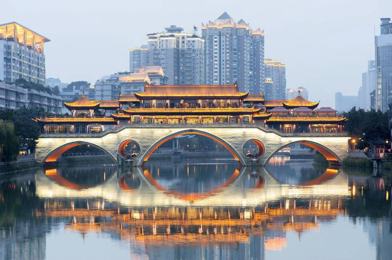 Anshun bridge with lights reflecting in the river at dawn with buildings in blue haze in the background, Chengdu, China