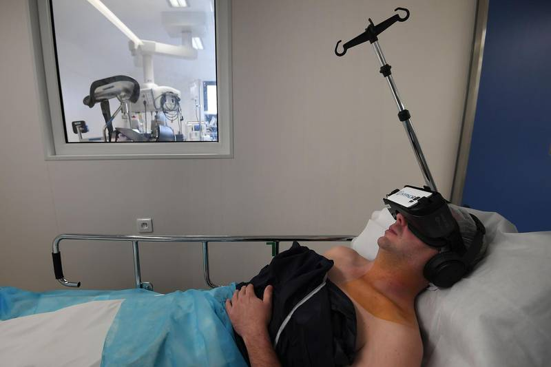 A patient wearing a virtual reality headset received a local anaesthesia by an hypnotherapist anaesthetist; before a surgery, at the Rhéna Clinic on October 25, 2018 in Strasbourg, eastern France. HypnoVR, founded in 2016 by two anaesthetists and an entrepreneur, provides software and virtual reality headsets allowing the hypnotherapist to treat several patients. / AFP / Frederick FLORIN
