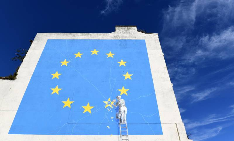 epaselect epa06920668 A view of a Brexit-inspired mural by anonymous British street artist Banksy depicting the European flag in Dover, Britain, 31 July 2018. The graffiti that appeared on a building near Dover's ferry terminal shows a worker removing one of the 12 stars from the EU flag.  EPA/FACUNDO ARRIZABALAGA