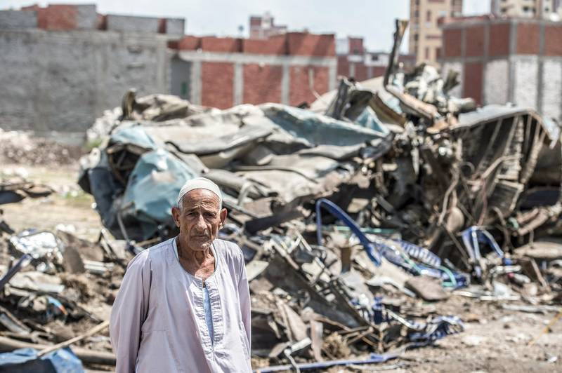 An Egyptian stands by the wreckage from the day before of a fatal rail collision in the area of Khorshid on the outskirts of Egypt's Mediterranean city of Alexandria from the day before, on August 12, 2017. - The toll from the accident on August 11, 2017, when two trains hurtled into each other near Egypt's second-largest city, has risen to 40 dead and 123 wounded, said health ministry spokesman Khaled Moujahed, as local media said the number of fatalities was likely to rise. (Photo by KHALED DESOUKI / AFP)