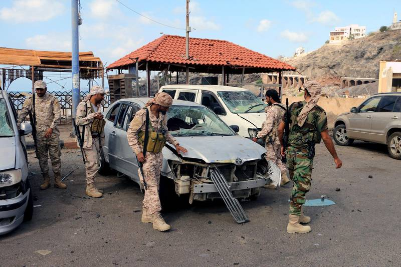 epa06563818 Yemeni soldiers inspect the site of car bomb attacks outside the headquarters of a counter-terrorism unit in the southern port city of Aden, Yemen, 25 February 2018. According to reports, at least 14 Yemenis were killed and 40 others wounded when two car suicide bombers struck the entrance of the headquarters of a counter-terrorism unit in Aden.  EPA/STRINGER