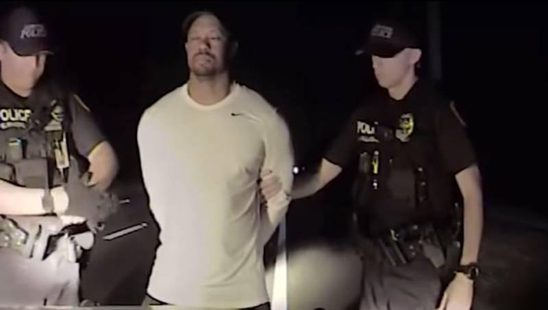 """This still image from a dashcam video released by the Jupiter, Florida, Police Department on May 31, 2017, shows Jupiter police offices arresting golfer Tiger Woods on May 29. - The video, from a dashboard camera in the vehicle of Jupiter police officers, shows Woods wobbling as he tries to walk along a straight line in a field sobriety test. Woods has blamed the DUI arrest near his home on an adverse reaction to prescription medication. (Photo by HO / Jupiter Police Department / AFP) / RESTRICTED TO EDITORIAL USE - MANDATORY CREDIT """"AFP PHOTO / Jupiter Police Department"""" - NO MARKETING NO ADVERTISING CAMPAIGNS - DISTRIBUTED AS A SERVICE TO CLIENTS"""