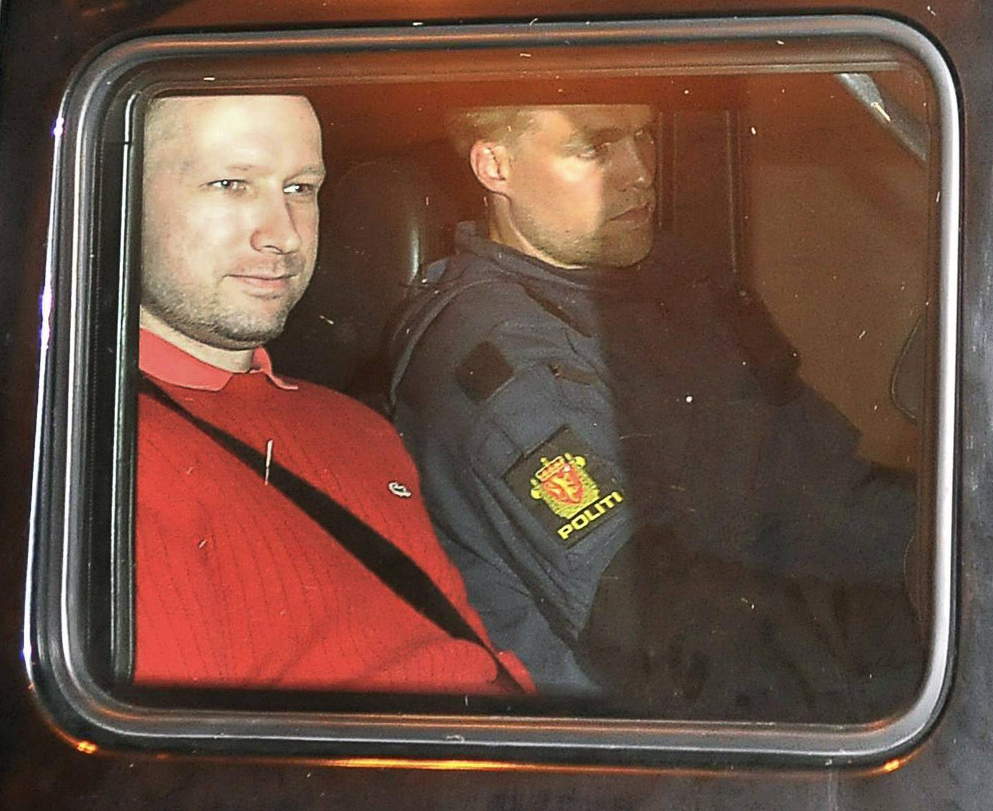 Bomb and terror suspect Anders Behring Breivik (red top) leaves the courthouse  in a police car  in Oslo on July 25, 2011, after the hearing to decide his further detention.  Breivik will be held in solitary confinement for the first four weeks, with a ban on all communication with the outside world in a bid to aid a police investigation into his acts. AFP Photo Jon-Are Berg-Jacobsen / Aftenposten  *** Local Caption ***  490497-01-08.jpg