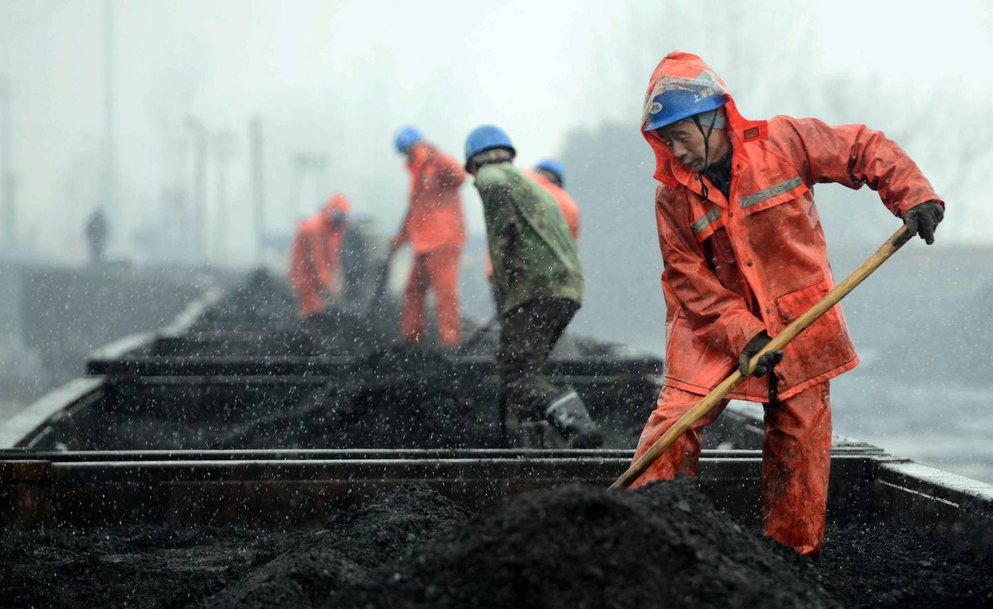 JIUJIANG, CHINA - JANUARY 22:  (CHINA OUT) Workers load coal onto railcars during a snowfall at a railway station on January 22, 2016 in Jiujiang, China. The National Meteorological Center (NMC) on Friday issued a yellow alert for blizzards that are expected to sweep China's northern, central and eastern regions.  (Photo by VCG/VCG via Getty Images)