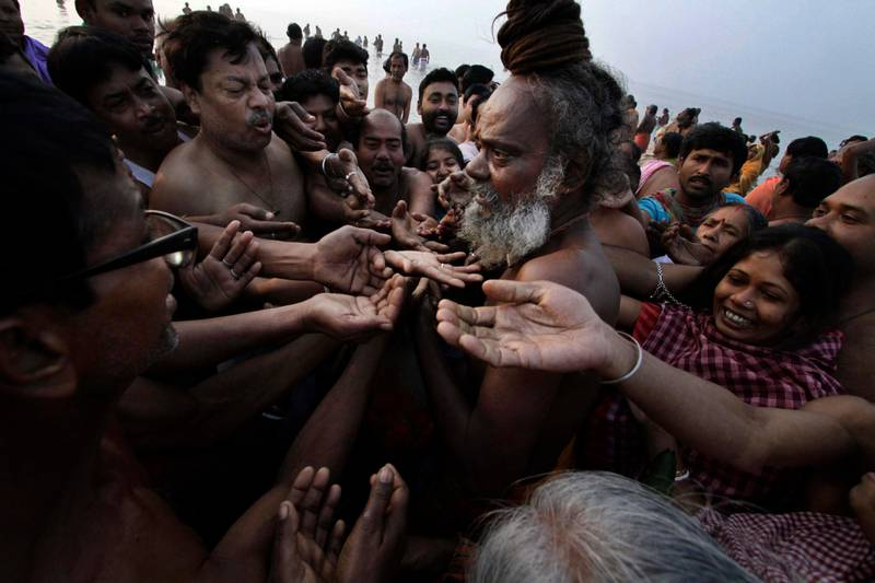 """Pilgrims seek blessings from a Hindu holy man at Gangasagar, India, Monday, Jan. 14, 2013. Thousands of Hindu pilgrims bathed at Gangasagar, the confluence of Hindu holy river Ganges and the Bay of Bengal, 140 kilometers (87 miles) south of Kolkata, an act that is expected to help them wash off their sins on the auspicious occasion of Makar Sankranti, as it is called in northern and eastern India. The day marks the beginning of """"uttarayana"""" or the suns northward movement, considered to be very auspicious astrologically. (AP Photo/Bikas Das) *** Local Caption ***  India Hindu Festival.JPEG-0c37f.jpg"""