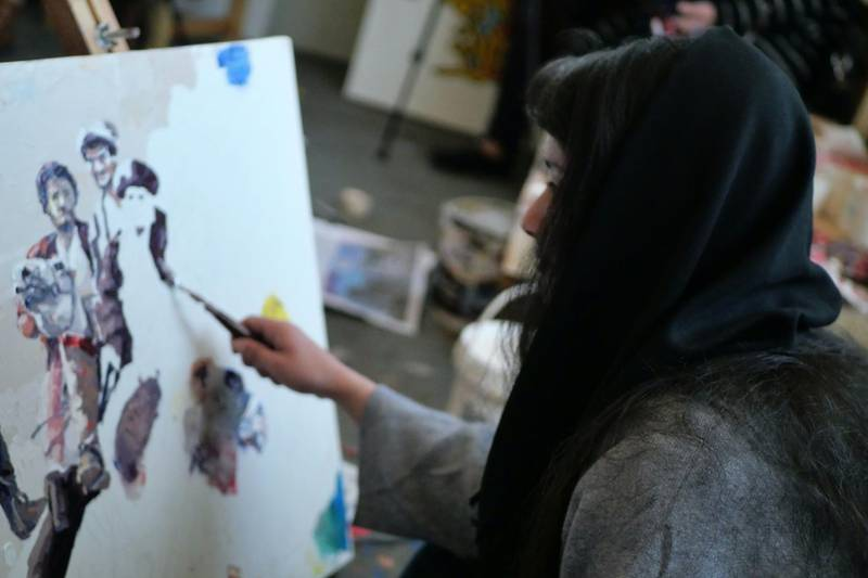 Pictured: A woman artist paints at ArtLords headquarters in Kabul. Photo by Charlie Faulkner February 2021