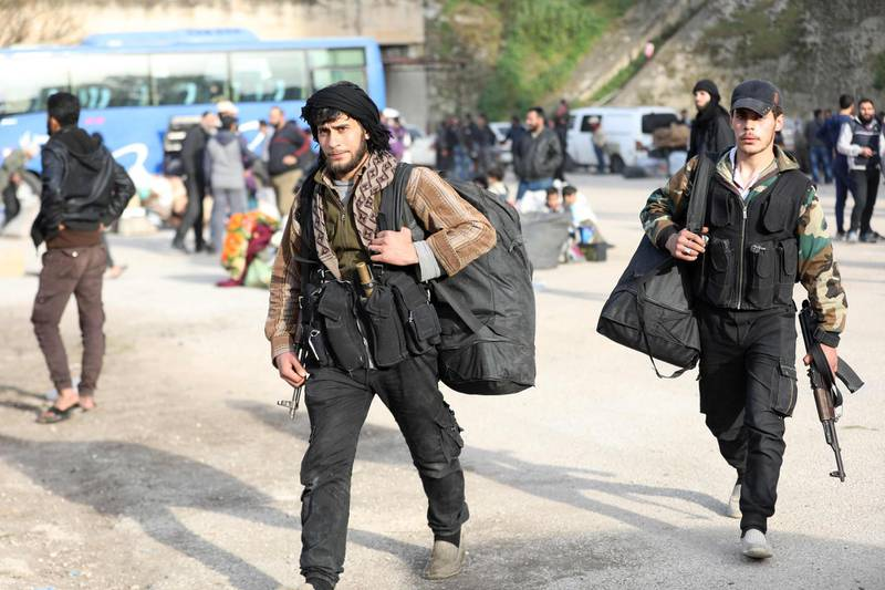 Rebel fighters are seen upon their arrival in the Qalaat al-Madiq village in the province of Hama, on March 13, 2018, after being evacuated from the Qadam neighbourhood on the outskirts of Damascus under a deal agreed between the government and opposition fighters.  With Syria's war set to enter its eighth year this week, fighting continues on several fronts, including around Afrin and in Eastern Ghouta near Damascus, where dozens of civilians including people with medical conditions were evacuated. / AFP PHOTO / OMAR HAJ KADOUR