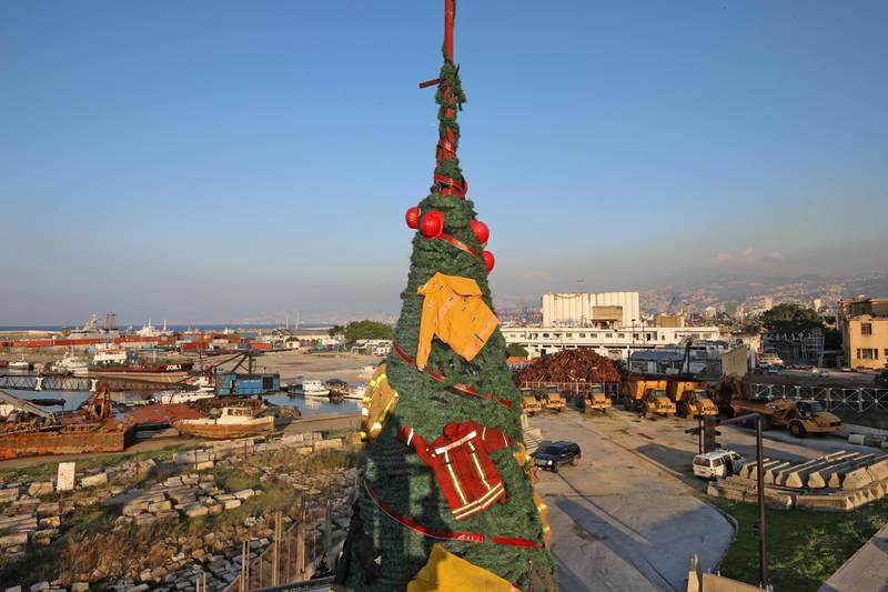 """Members of the Lebanese Civil Defense erect a Christmas tree by Lebanese artist Hayat Nazer, decorated with uniforms of firefighters, as a way to pay tribute to colleagues who were killed in the August 4 port explosion, in the Lebanese capital Beirut's harbour, on December 18, 2020. (Photo by ANWAR AMRO / AFP) / """"The erroneous mention[s] appearing in the metadata of this photo by ANWAR AMRO has been modified in AFP systems in the following manner: [uniforms of firefighters as a way to pay tribute ] instead of [the uniforms of firefighters who were killed]. Please immediately remove the erroneous mention[s] from all your online services and delete it (them) from your servers. If you have been authorized by AFP to distribute it (them) to third parties, please ensure that the same actions are carried out by them. Failure to promptly comply with these instructions will entail liability on your part for any continued or post notification usage. Therefore we thank you very much for all your attention and prompt action. We are sorry for the inconvenience this notification may cause and remain at your disposal for any further information you may require."""""""